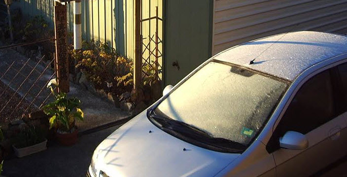 car parked facing east to defrost snow from the sun