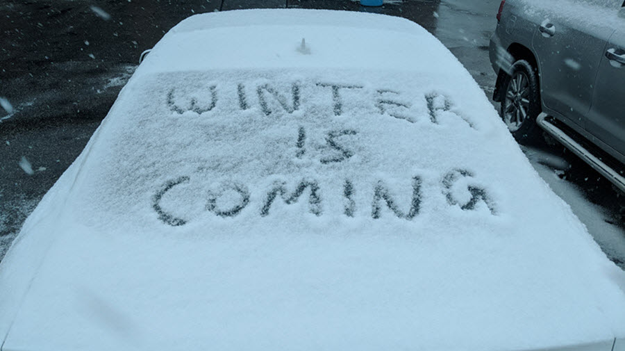 winter is coming written in snow on a car