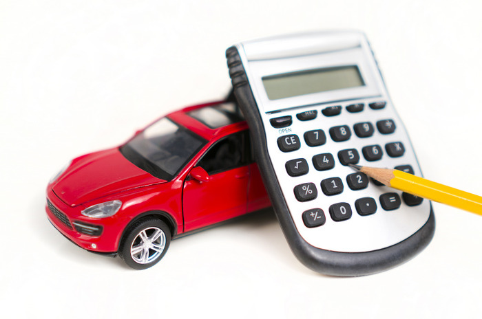Red toy car, calculator and pencil over a white background to signify car financing for car buyers